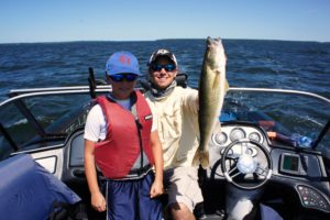 Young man with his great Leech Lake walleye held by Guide Toby.